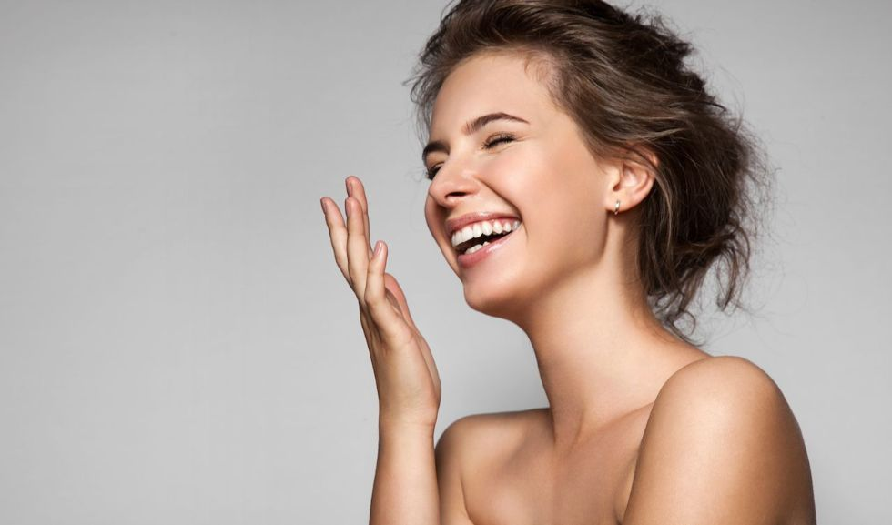 Une femme rit sur un fond gris