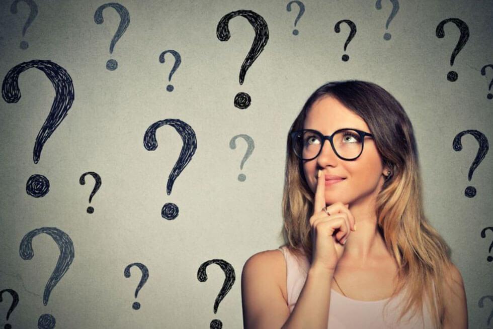 Une femme avec un doigt sur la bouche se tient devant un mur ou sont dessinés des points d'interrogations.