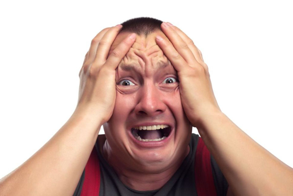 Un homme se tient la tête en faisant mine de crier pour signifier l'irritabilité