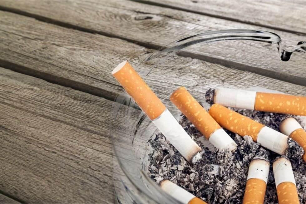 Un cendrier avec une multitude de mégots écrasés et une cigarette éteinte est posée par-dessus