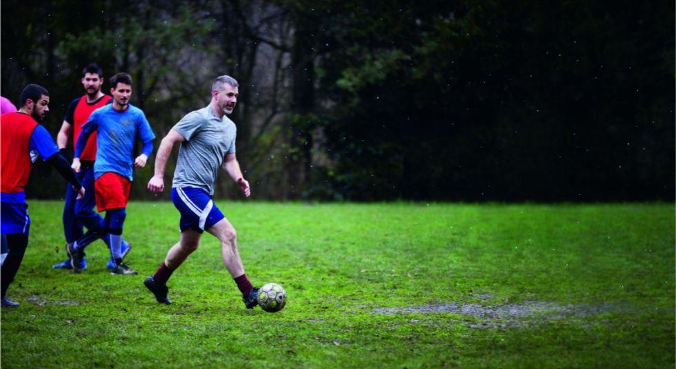 Photo d'un groupe d'homme jouant au football sur l'herbe