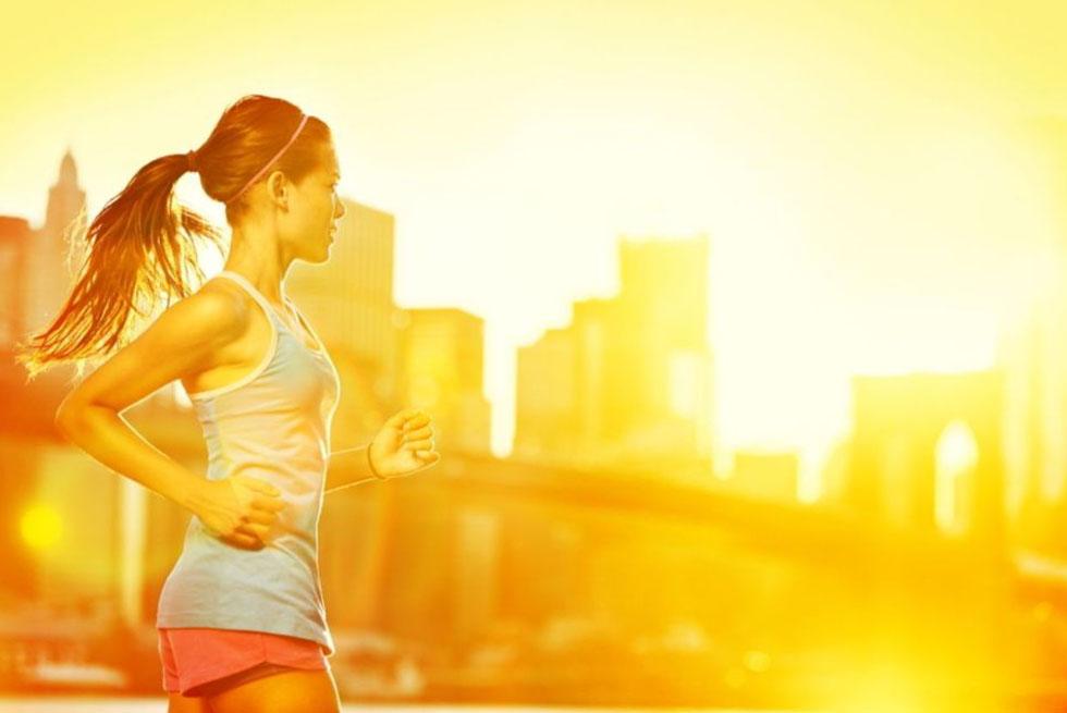 Une jeune femme cours devant un levé de soleil sur une foret