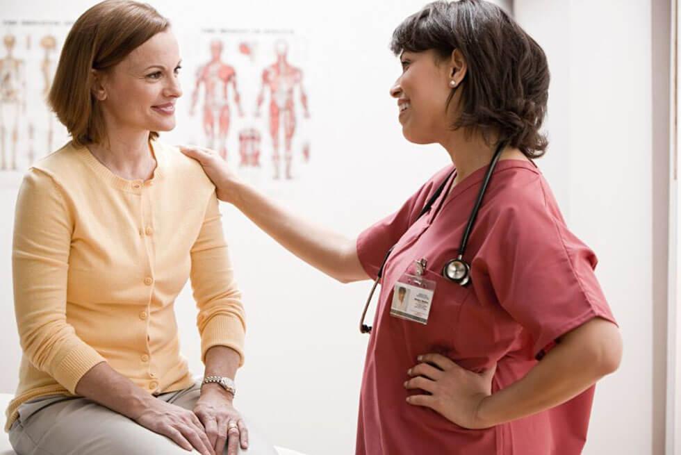 Une femme assise parle à un médecin